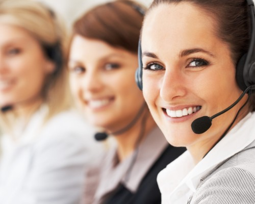 Closeup of customer service representative with colleagues in background